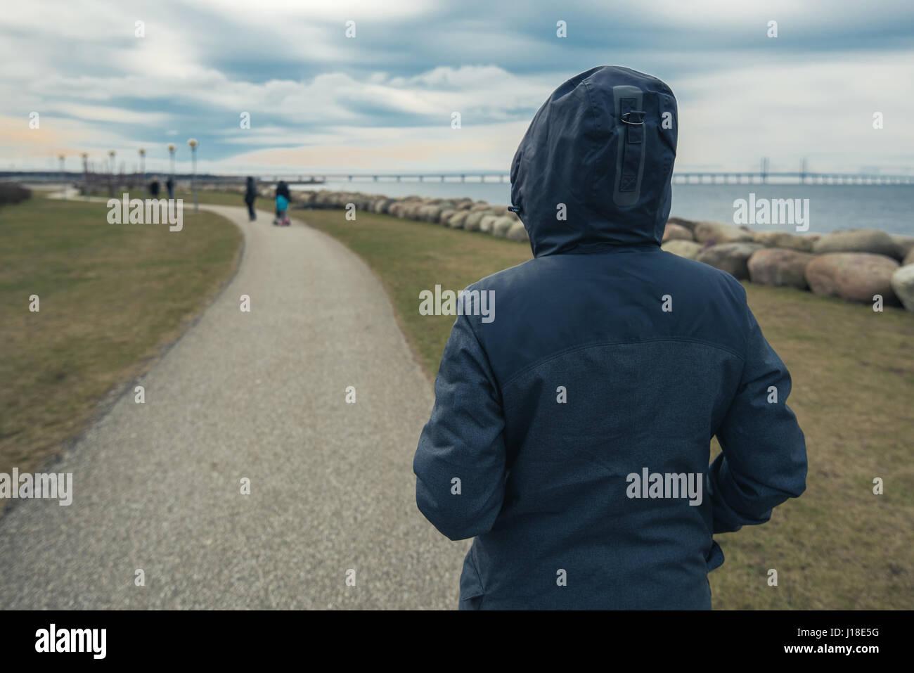 Einsam mit Kapuze weibliche Person von hinten stand am Ufer und sah in Entfernung an einem kalten Wintertag, Konzept Stockfoto