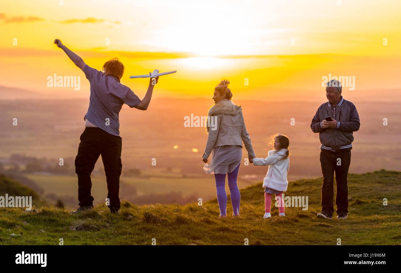 Familie in der Landschaft in den Abend im Frühjahr, wenn die Sonne untergeht, werfen ein Spielzeug Flugzeug Stockbild