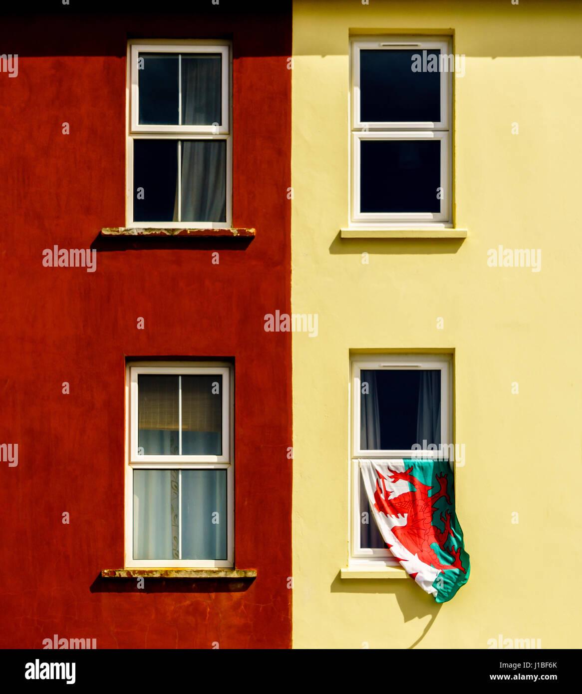 Die walisische Flagge hängen von einem Fenster in Aberystwyth, Wales Stockbild