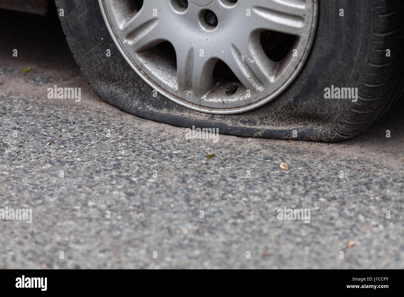 Platter Reifen auf der Straße Stockfotografie - Alamy