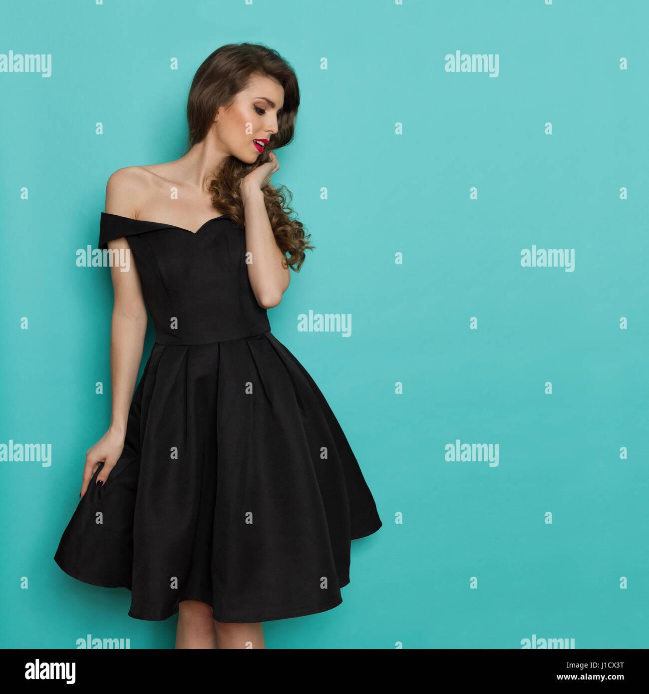 schöne junge frau in eleganten schwarzen cocktailkleid sucht