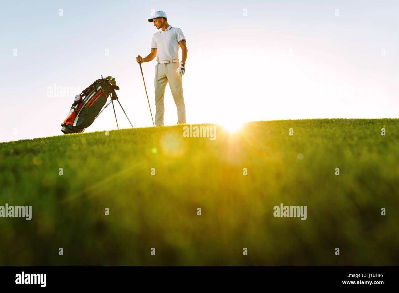 Gesamte Länge der Golfspieler, die Tasche auf Feld an sonnigen Tag stehend betrachten. Niedrigen Winkel Schuss Stockbild