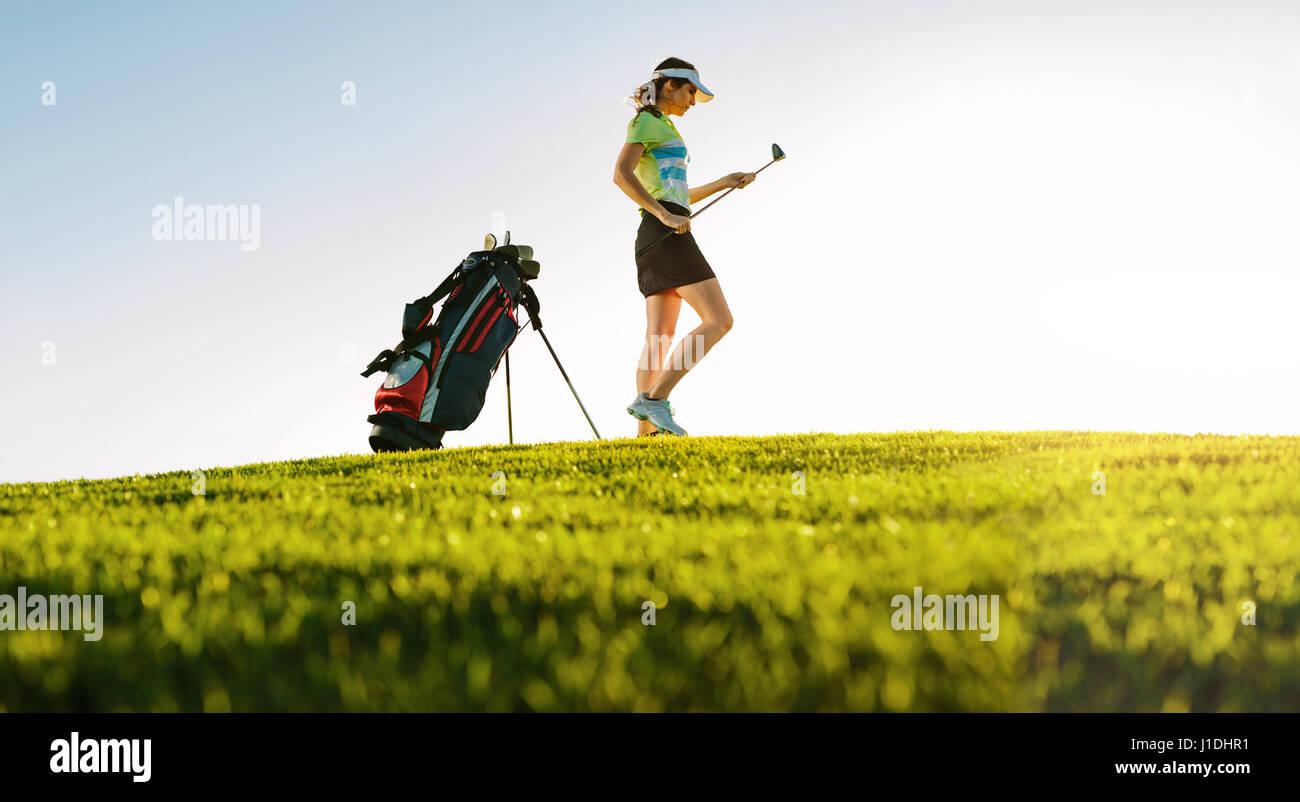 Niedrigen Winkel Schuss professionelle weibliche Golfer am Golfplatz. Gesamte Länge der Golfspieler mit Golf Stockbild