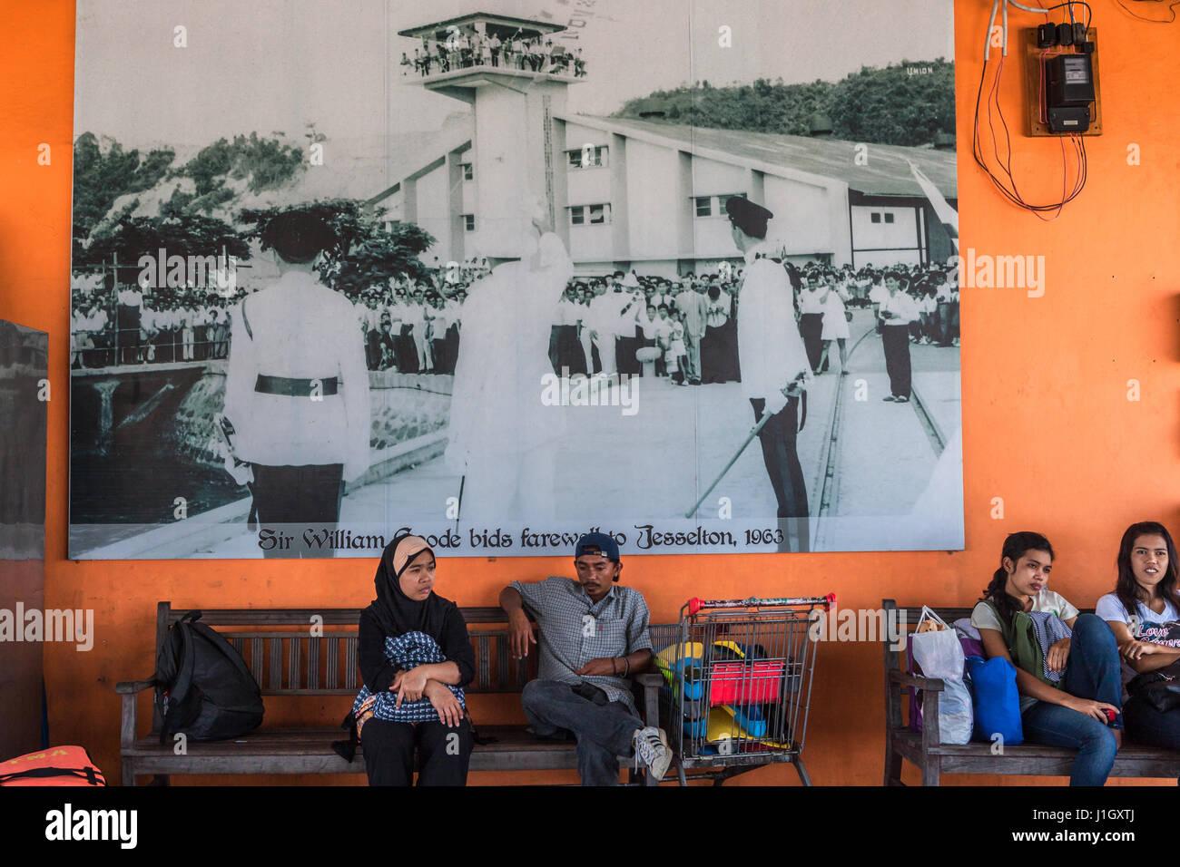 Fähre Passagiere in Jesselton Point Terminal von Kota Kinabalu mit einem historischen Foto an der Wand. © Stockbild