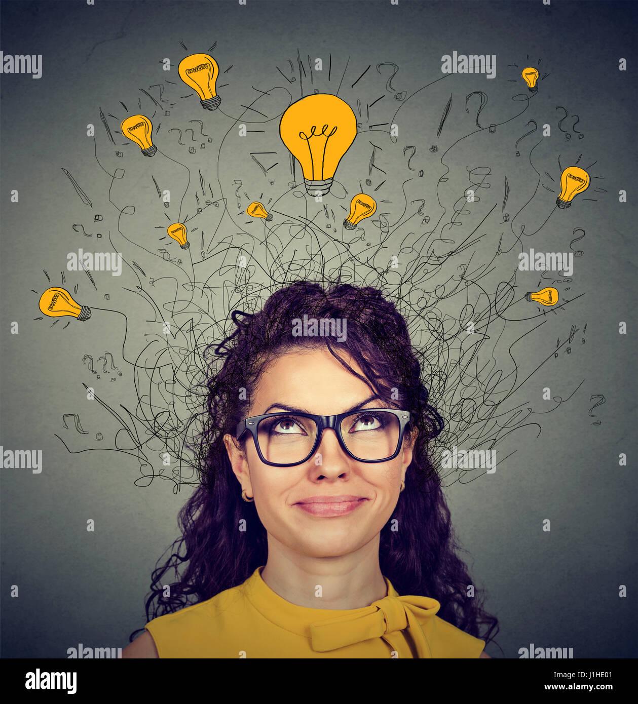 Junge Frau in Gläsern mit vielen Ideen, die Glühbirnen über Kopf nach oben isoliert auf graue Wand Stockbild