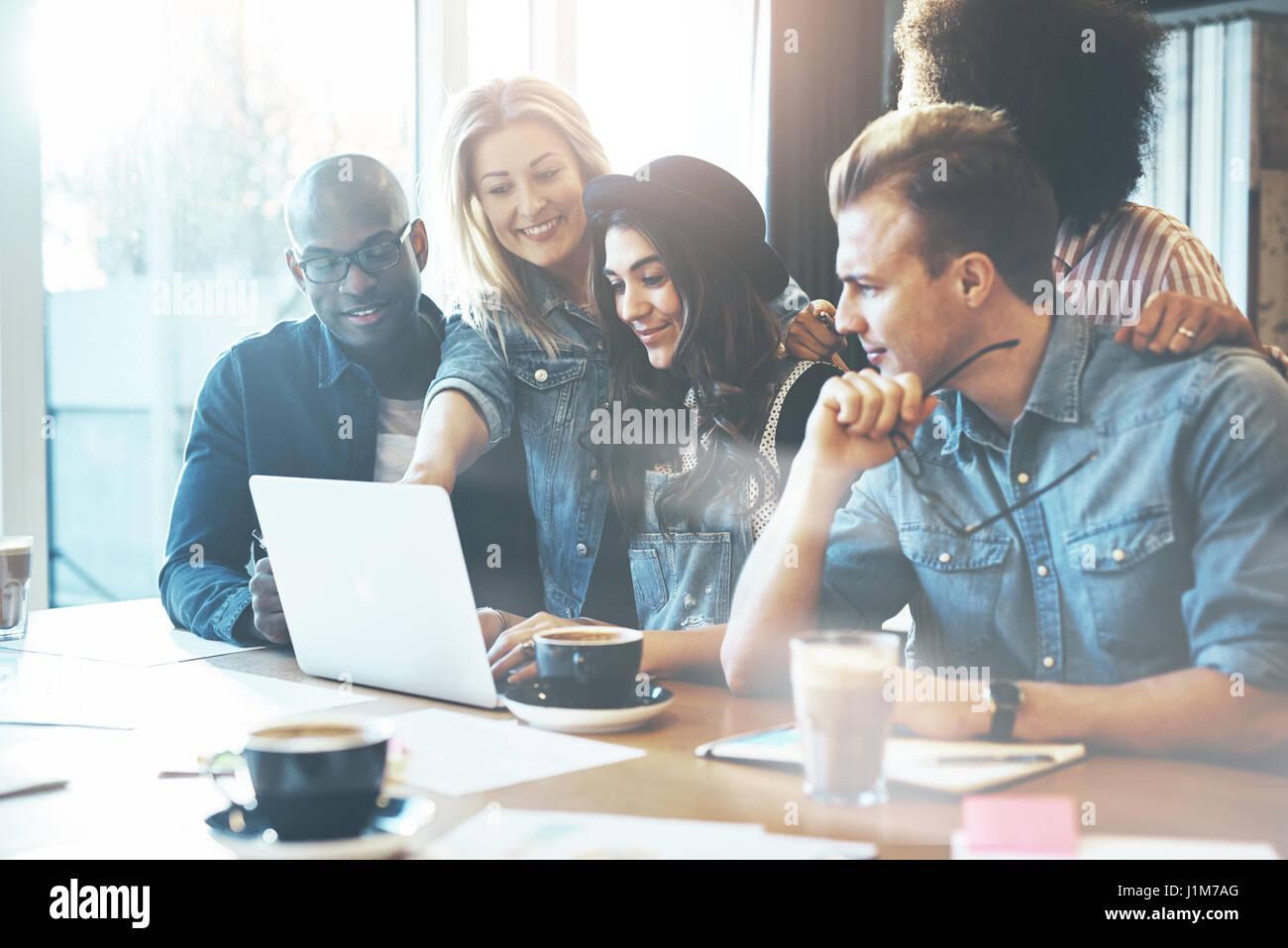 Frau zeigt Kollegen etwas auf Laptop-Computer, wie sie um einen Tisch versammeln Stockbild
