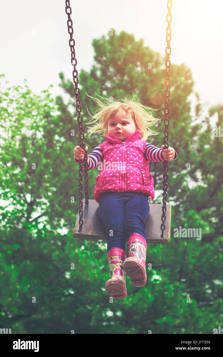 Kleinkind Mädchen auf der Schaukel Stockbild