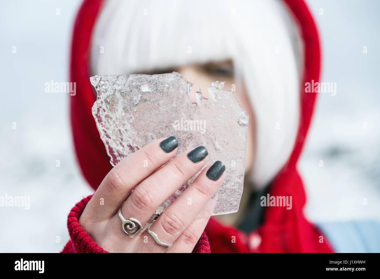 Junge Frau mit roter Haube und weiße Haare im winter Stockbild