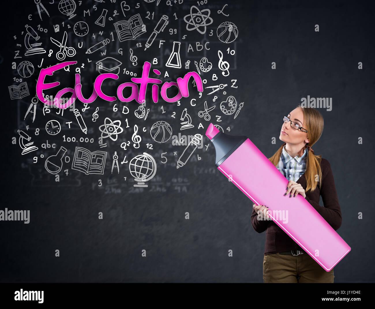 Schulmädchen mit großen Marker schreiben auf der Wand Wort Bildung Stockbild