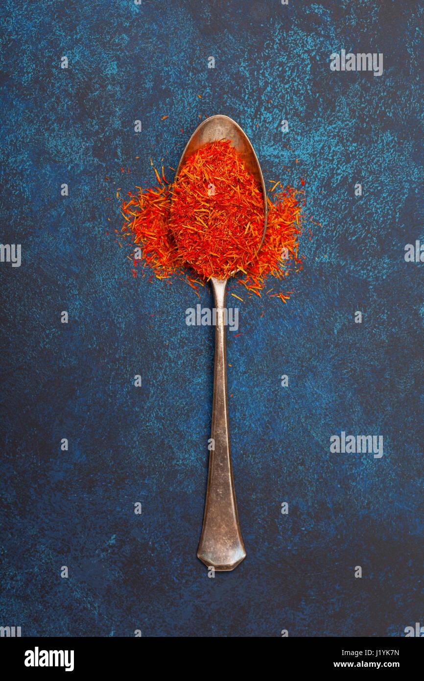 Safran in einen alten Silberlöffel auf blauem Grund. Ansicht von oben. Stockbild
