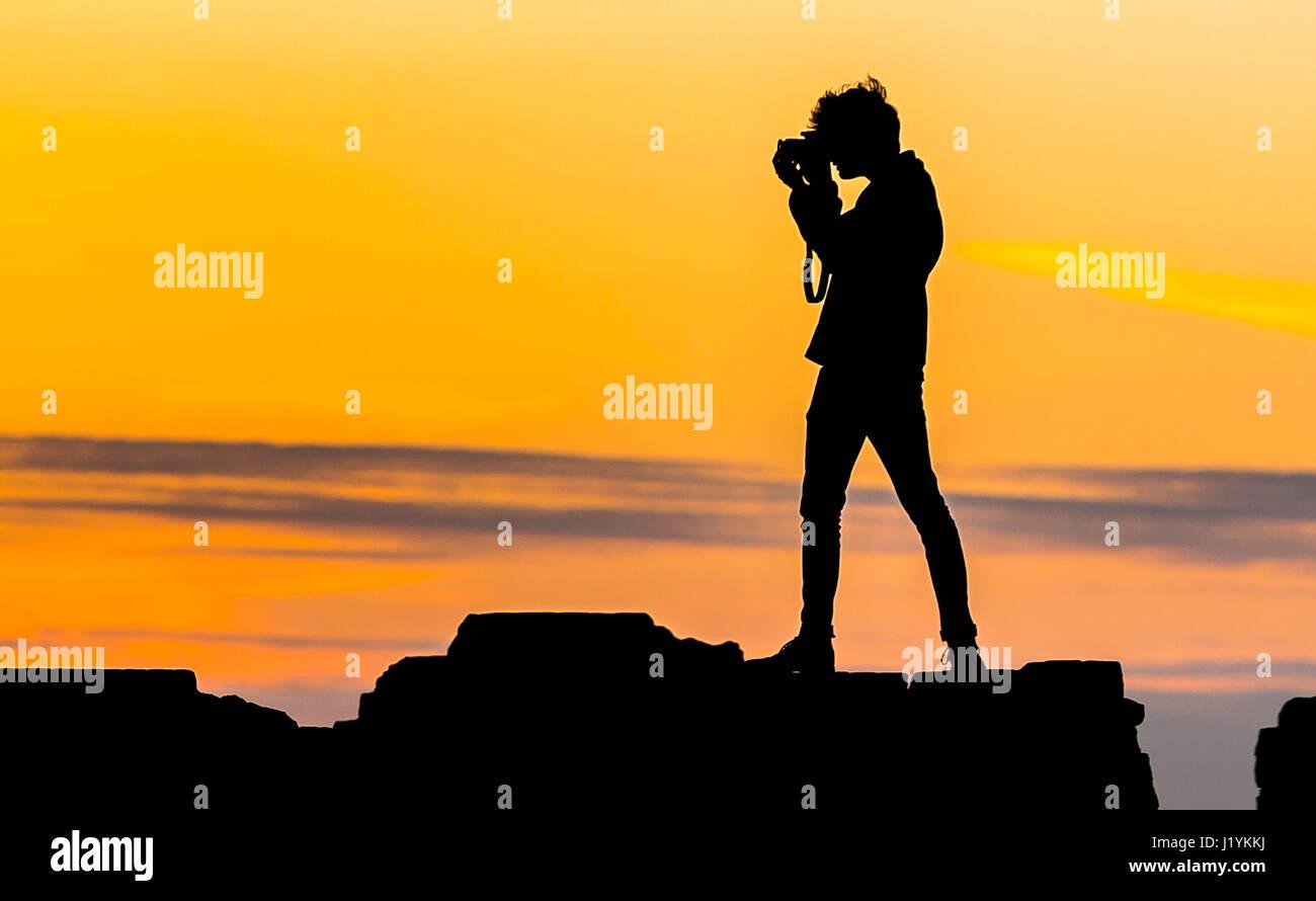 Abend-Fotograf. Silhouette eines jungen Fotografen fotografieren mit einer Kamera in den späten Abend, wenn Stockbild
