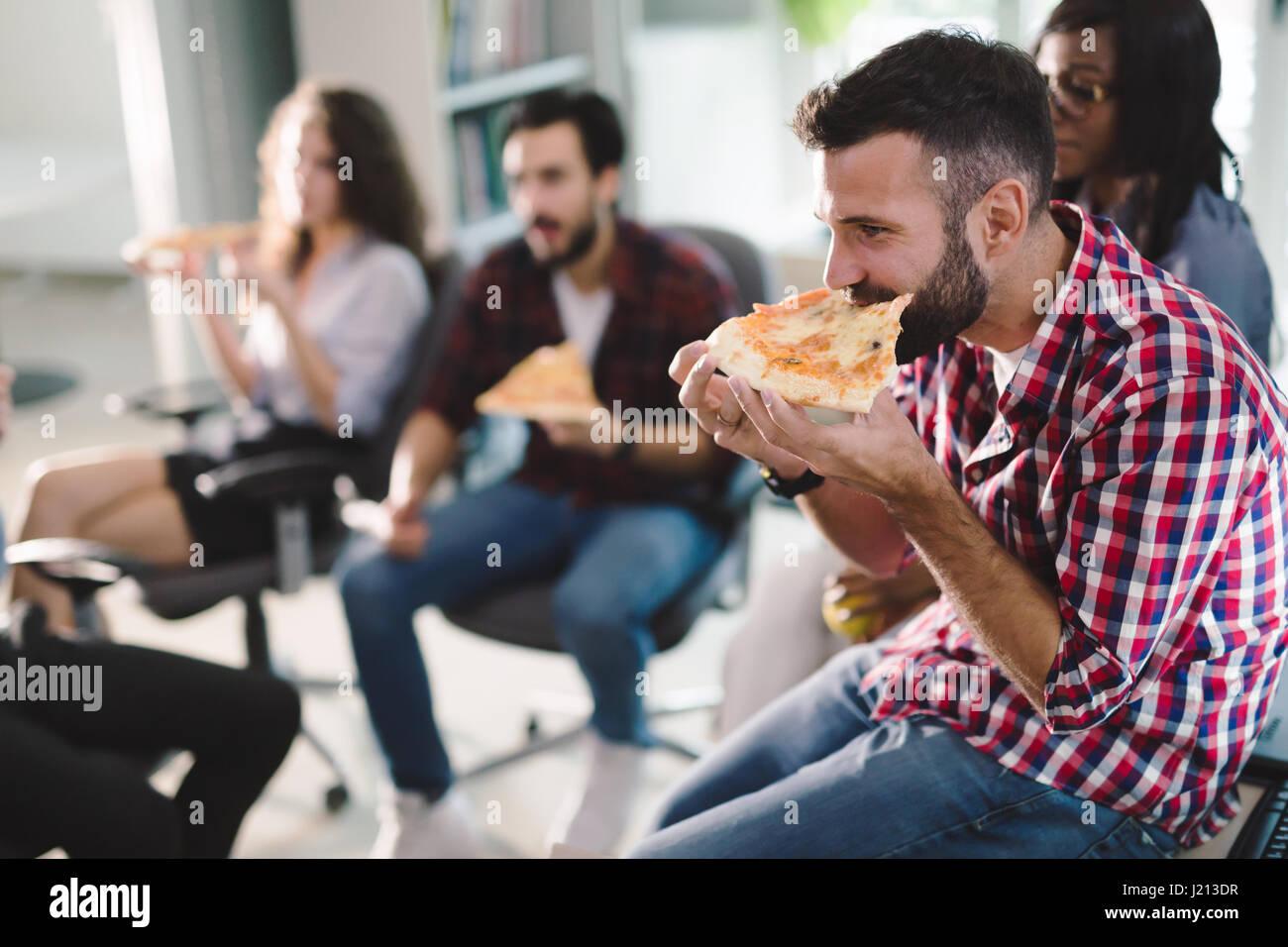 Kollegen Essen Pizza Wahrend Der Arbeit Im Buro Zu Brechen Stockfoto