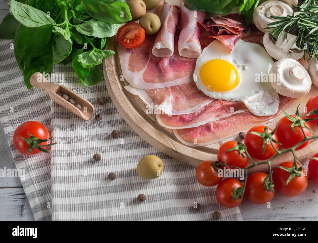 Gesunden mediterranen Frühstück Lebensmittel: gebratenen Eiern, Schinken, Strauchtomaten, Champignons, Stockbild