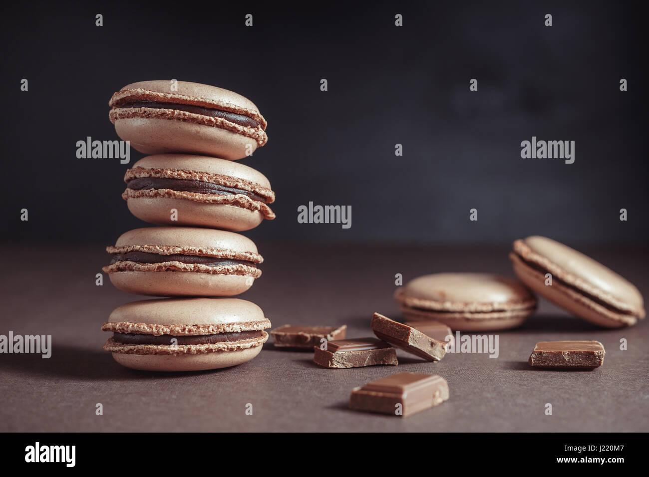 Stapel von Schokolade Pastell braune Macarons oder Makronen auf dunklem Hintergrund Stockbild