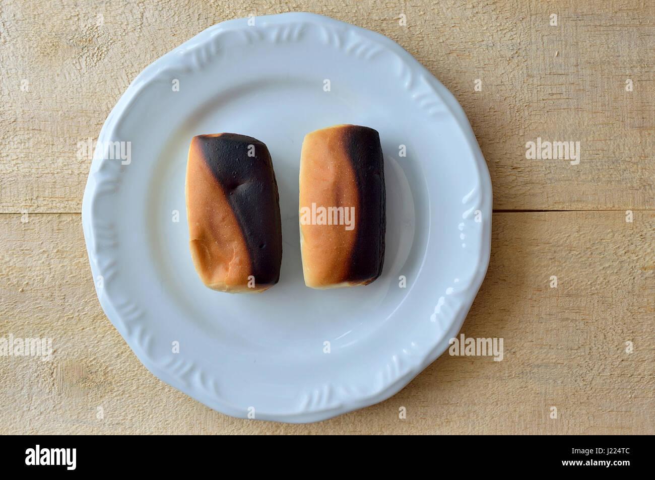Zwei verbrannt Brote auf einem weißen Teller über eine hölzerne Tischplatte Stockbild