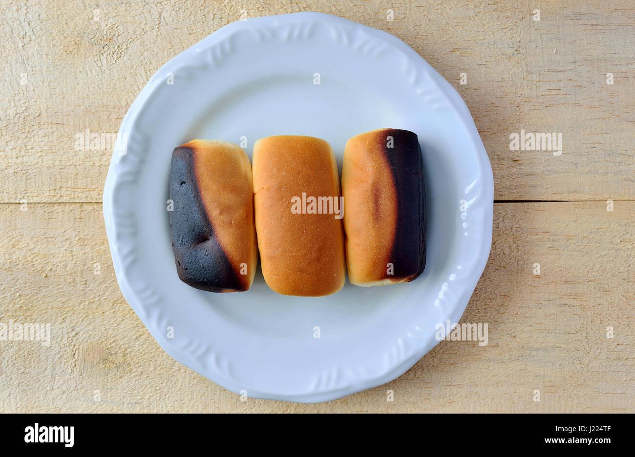 Zwei verbrannt Brot zusammen mit einem normalen Brot auf einem weißen Teller über eine hölzerne Tischplatte Stockbild