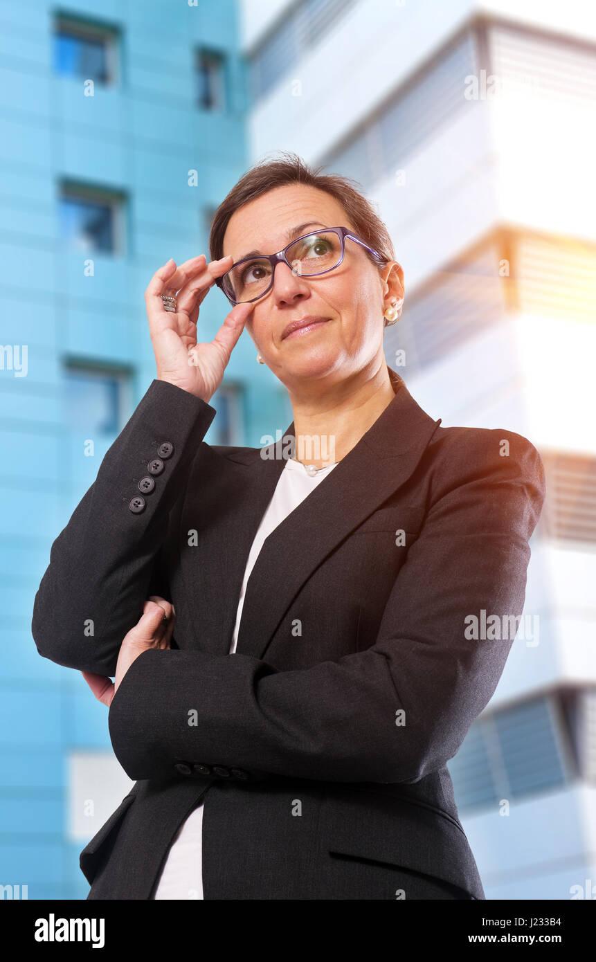 Brünette Business-Frau mit Brille posiert vor Bürogebäude Stockbild