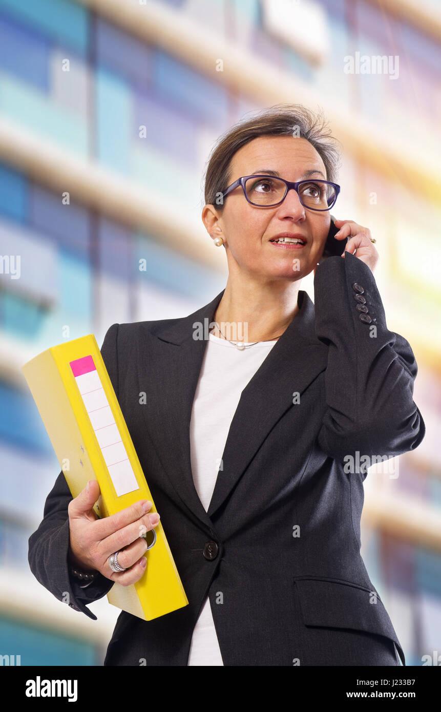 Brunette Geschäftsfrau mit gelben Ordner und Handy posiert vor Bürogebäude Stockbild