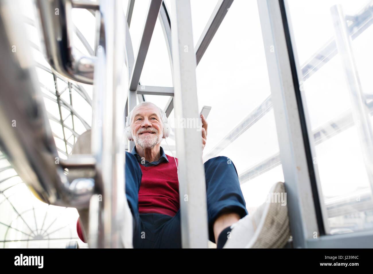 Ältere Mann mit Smartphone und Kopfhörer sitzen im Durchgang. Stockbild