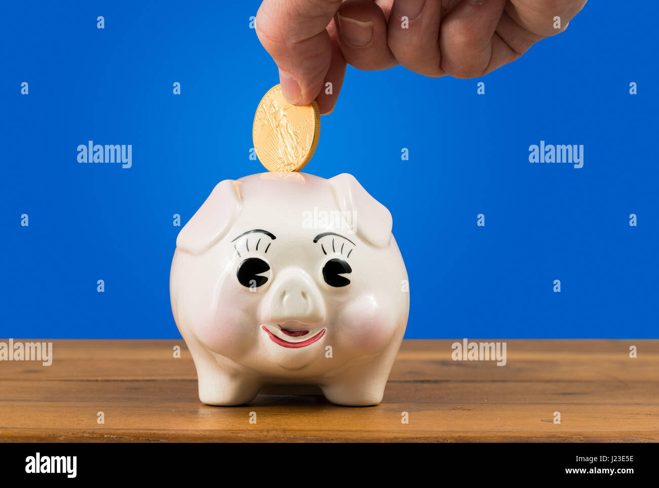 Sparschwein mit einer Hand, eine goldene Münze in - Einsparungen oder Investment-Konzept Stockbild