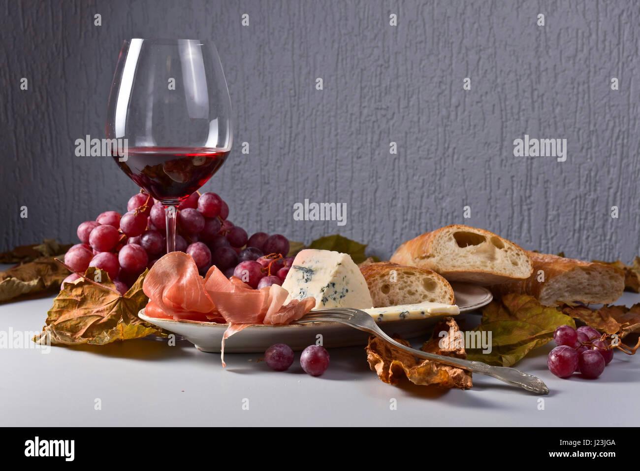 rotwein mit snack und trauben blauschimmelk se schinken und brot auf dem k chentisch. Black Bedroom Furniture Sets. Home Design Ideas