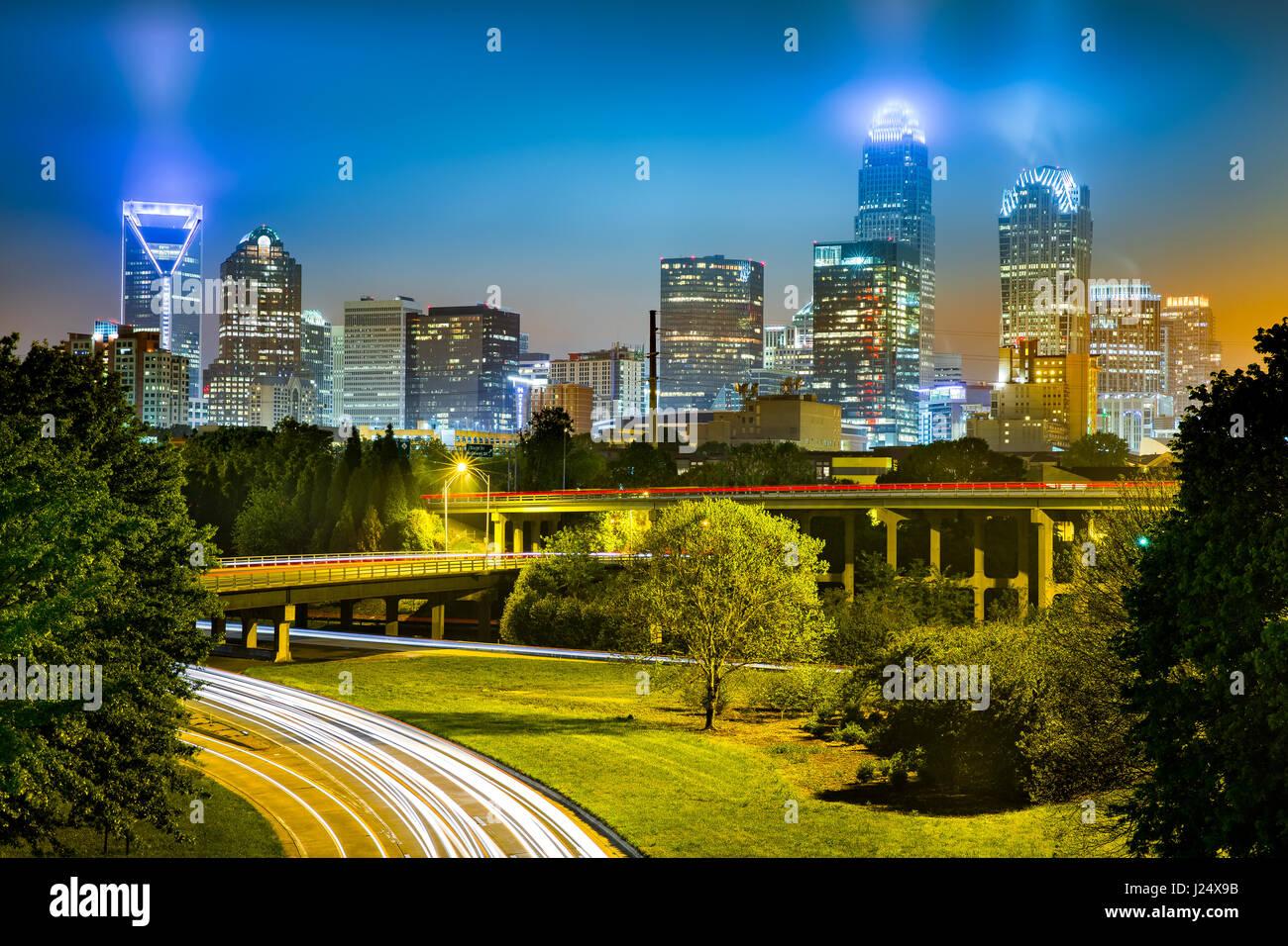 Ampel-Wanderwege in Charlotte, North Carolina. Die Skyline der Stadt leuchtet in einer nebligen Nacht. Stockfoto
