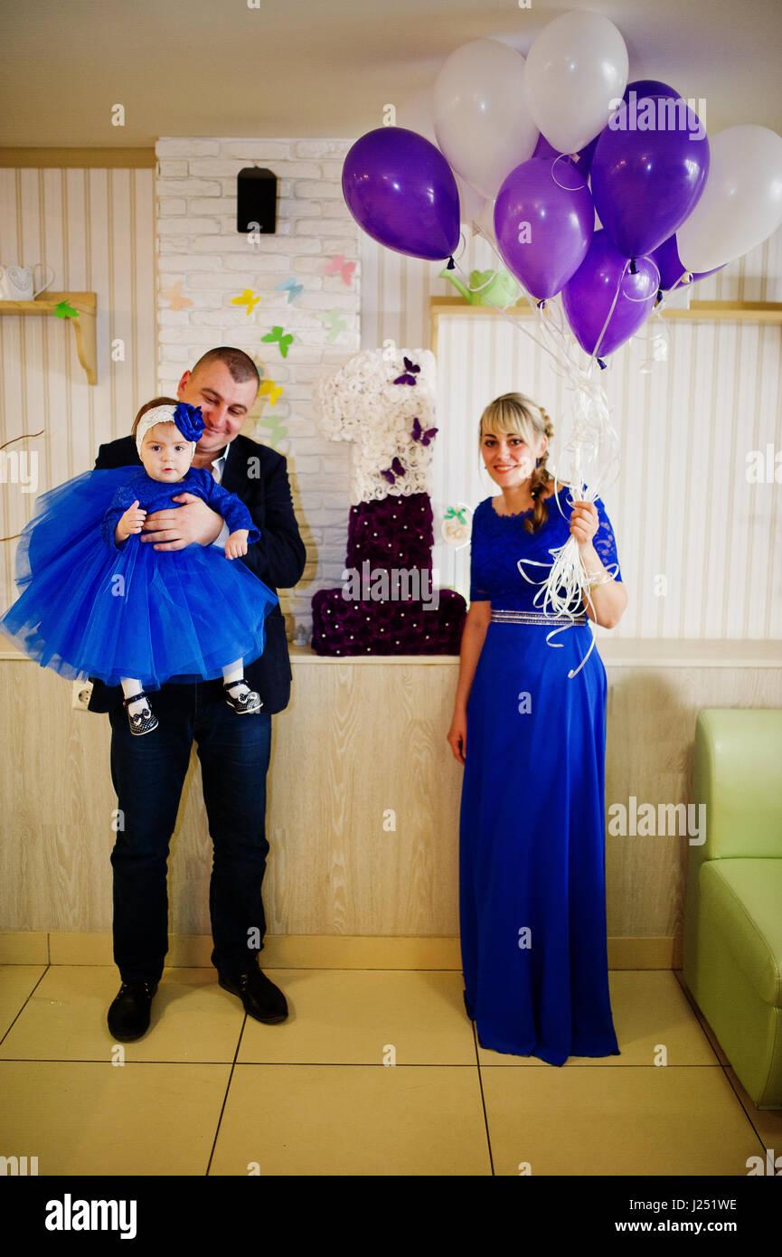 Niedliche kleine Baby Mädchen im blauen Kleid auf Hände von Vater ...