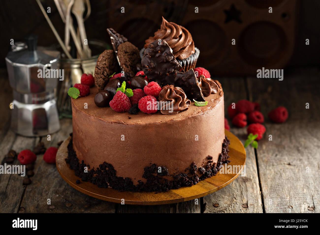 Schokoladenkuchen mit Ganache Glasur, festliche Dekorationen und Himbeere Stockbild