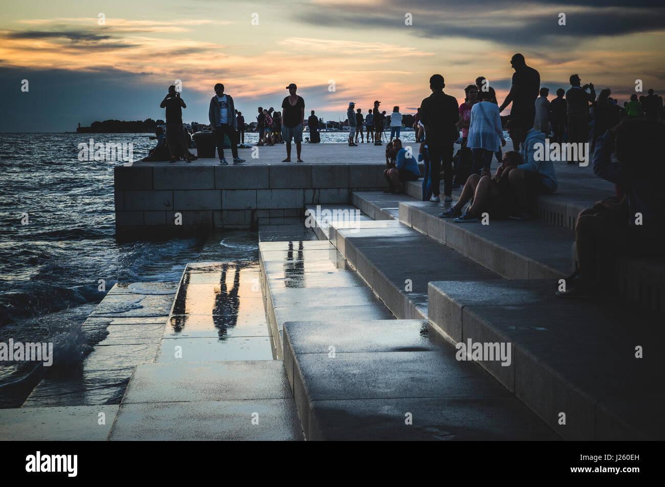 Massen um Meeresorgel versammelt, bei Sonnenuntergang, Zadar, Kroatien Stockbild