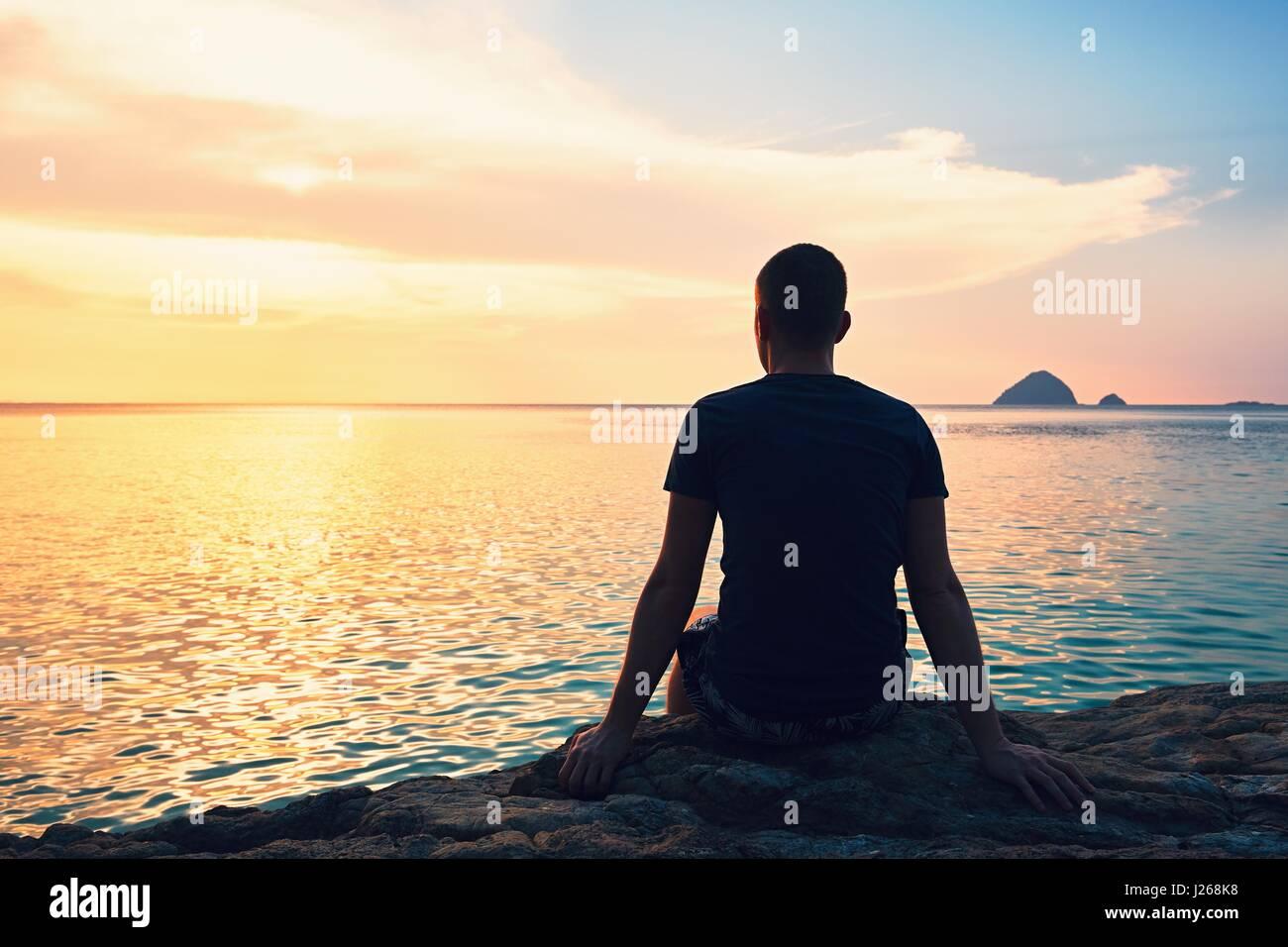Betrachtung auf den wunderschönen Sonnenuntergang. Silhouette des jungen Mannes am Strand. Stockbild