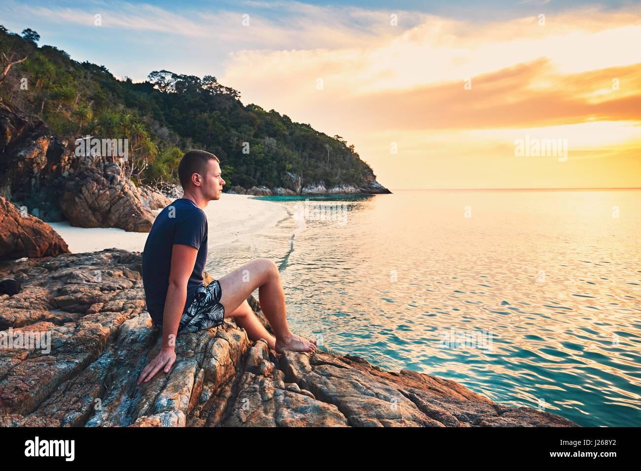 Betrachtung auf den Sonnenuntergang. Allein junger Mann am schönen Sandstrand. Stockbild