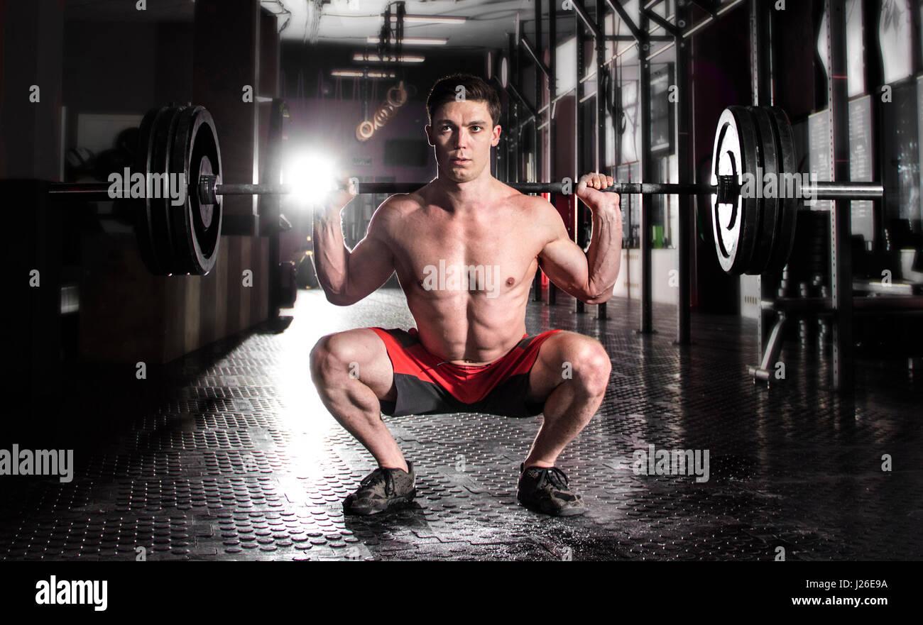 Attraktive muskuläre Crossfit Athlet Kniebeugen trainieren im mo Stockbild