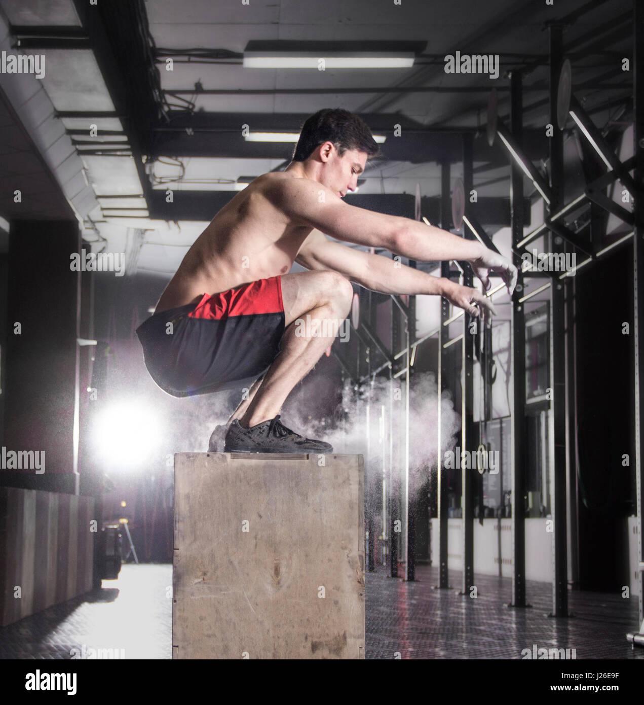 Passen Sie junge Männer-Kiste springen in einem Crossfit Gym. Sportler Datenzugriffsmöglichkeit Stockfoto