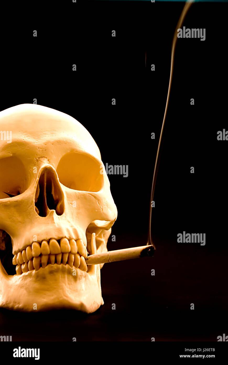 menschlicher Schädel mit einer Rauchen Zigarette in den Mund Stockbild