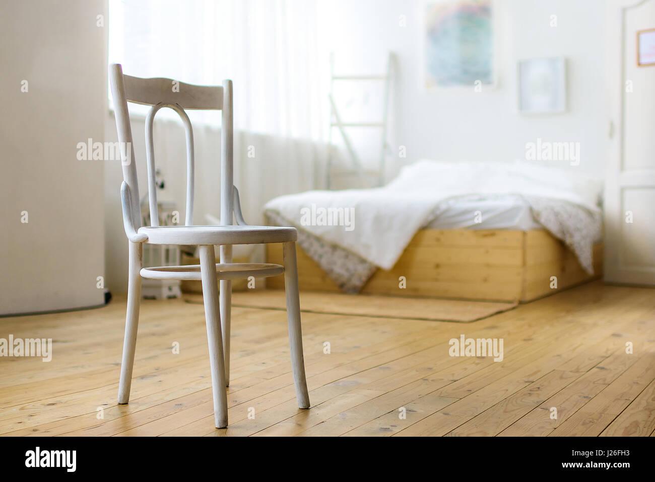 Weißer Stuhl im Schlafzimmer, Bett und Gemälde an der Wand ...