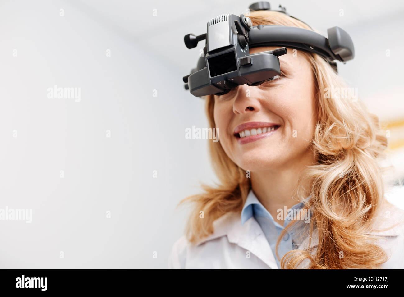 Sehr engagierte prominente Spezialisten tragen Ophthalmoskop Stockbild