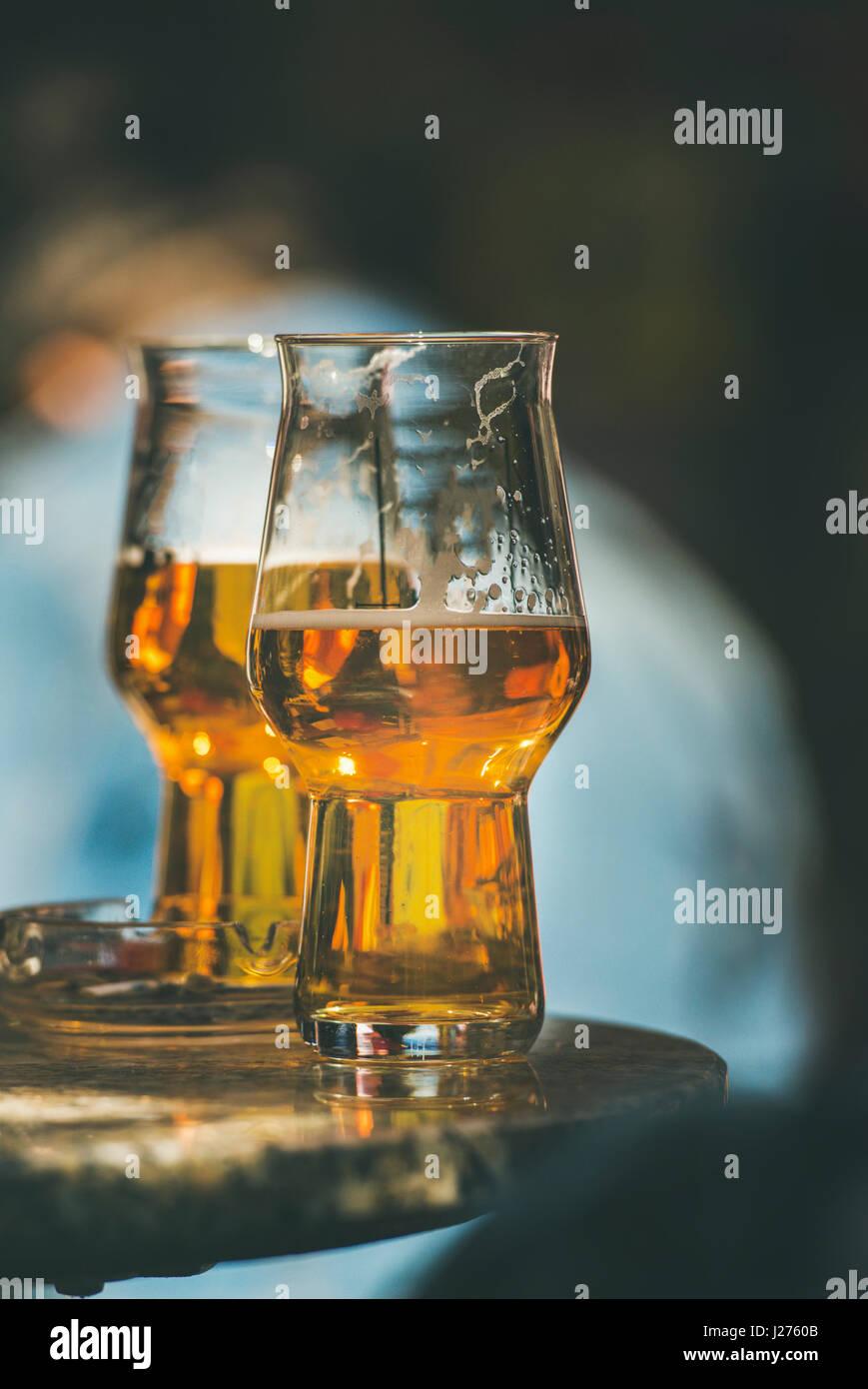 Zwei Gläser Bier auf einem Tisch in einem Straßencafé, Tiefenschärfe, vertikale Zusammensetzung Stockbild