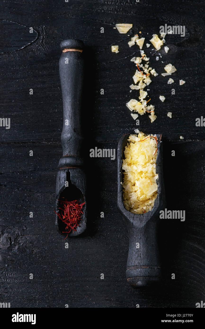 Gelber Safran Salz und Safran Gewürz in Holzlöffel über schwarzen verbrannten Holz Hintergrund. Draufsicht Stockbild