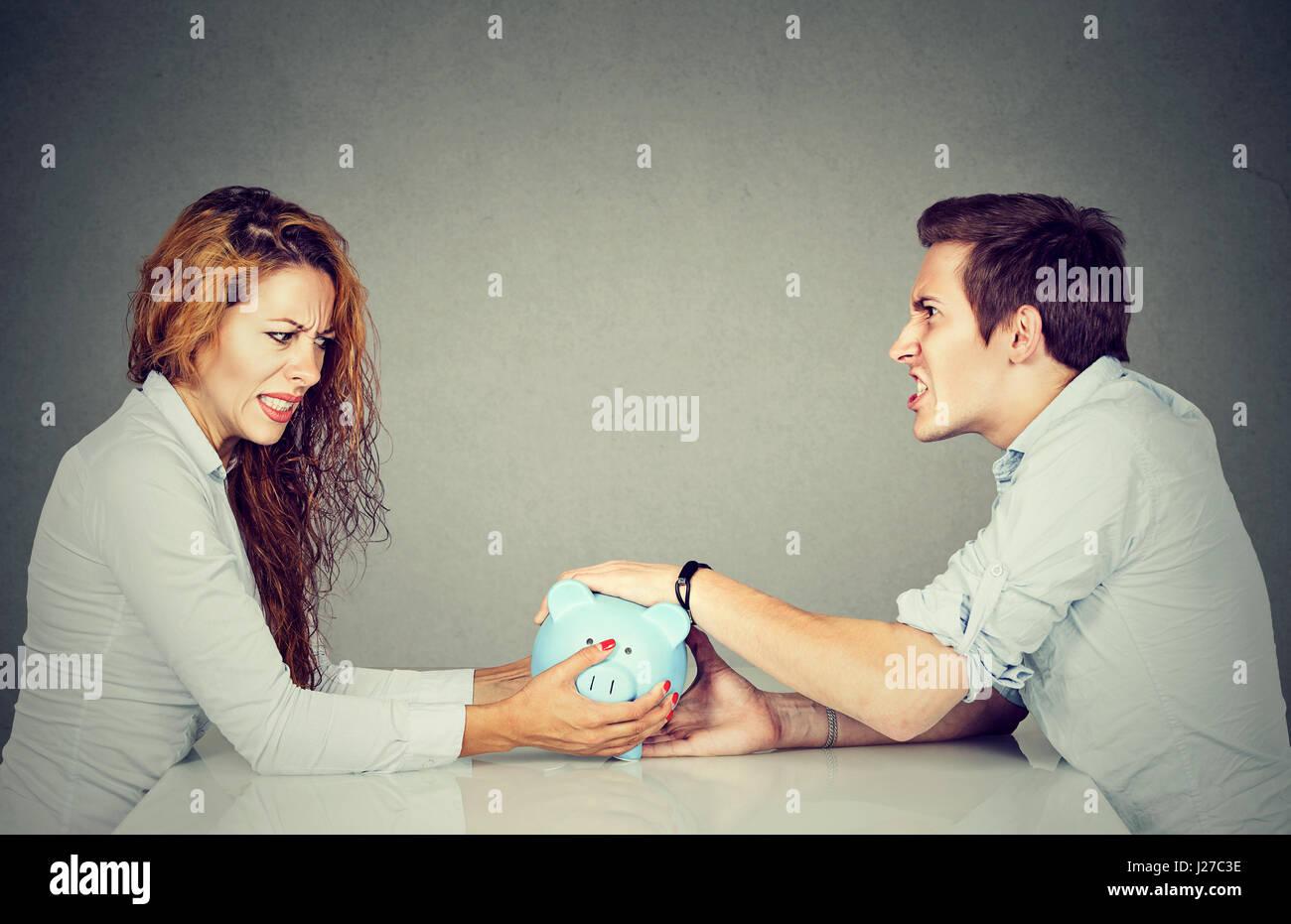 Finanzen in Scheidung-Konzept. Frau und Mann können nicht Siedlung Sparschwein sitzend am Tisch sahen einander Stockbild