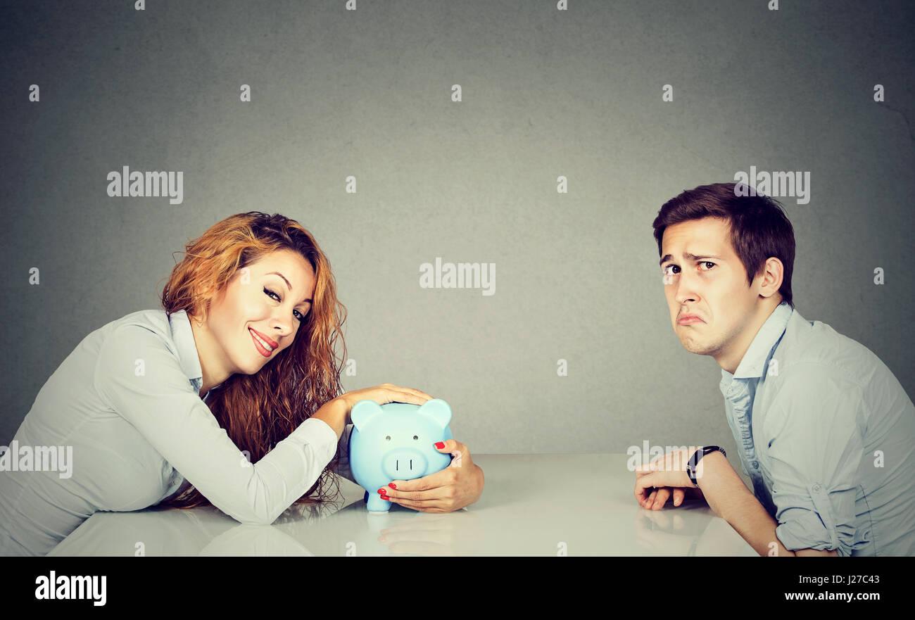 Finanzen in Scheidung-Konzept. Glückliche Frau mit Piggy Bank sitzen über der Tabelle von traurig verzweifelten Stockbild