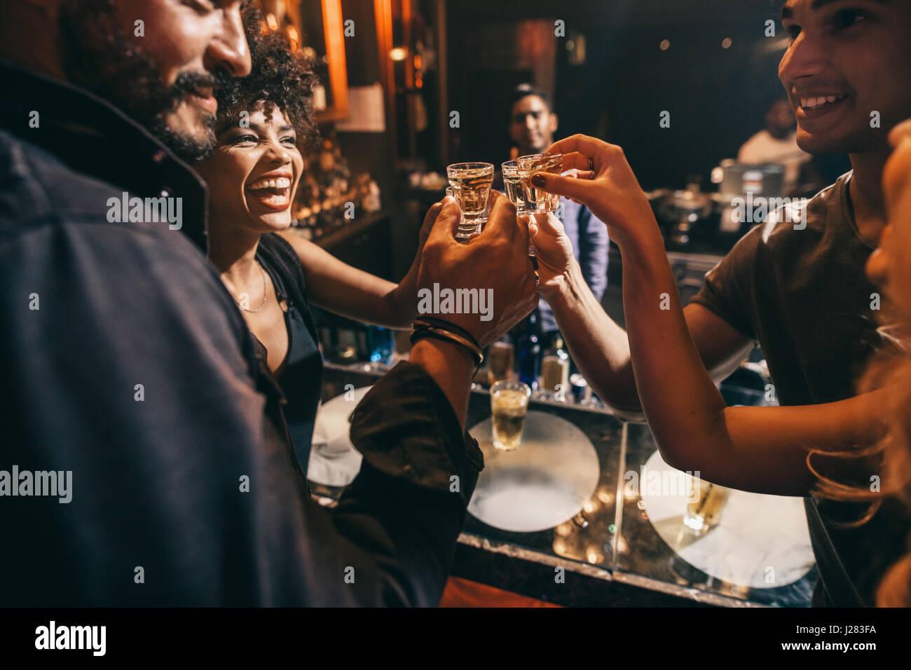 Freunde, die einander mit Aufnahmen von Wodka Toasten, wie sie einen entspannenden Abend in der Kneipe gemeinsam Stockbild