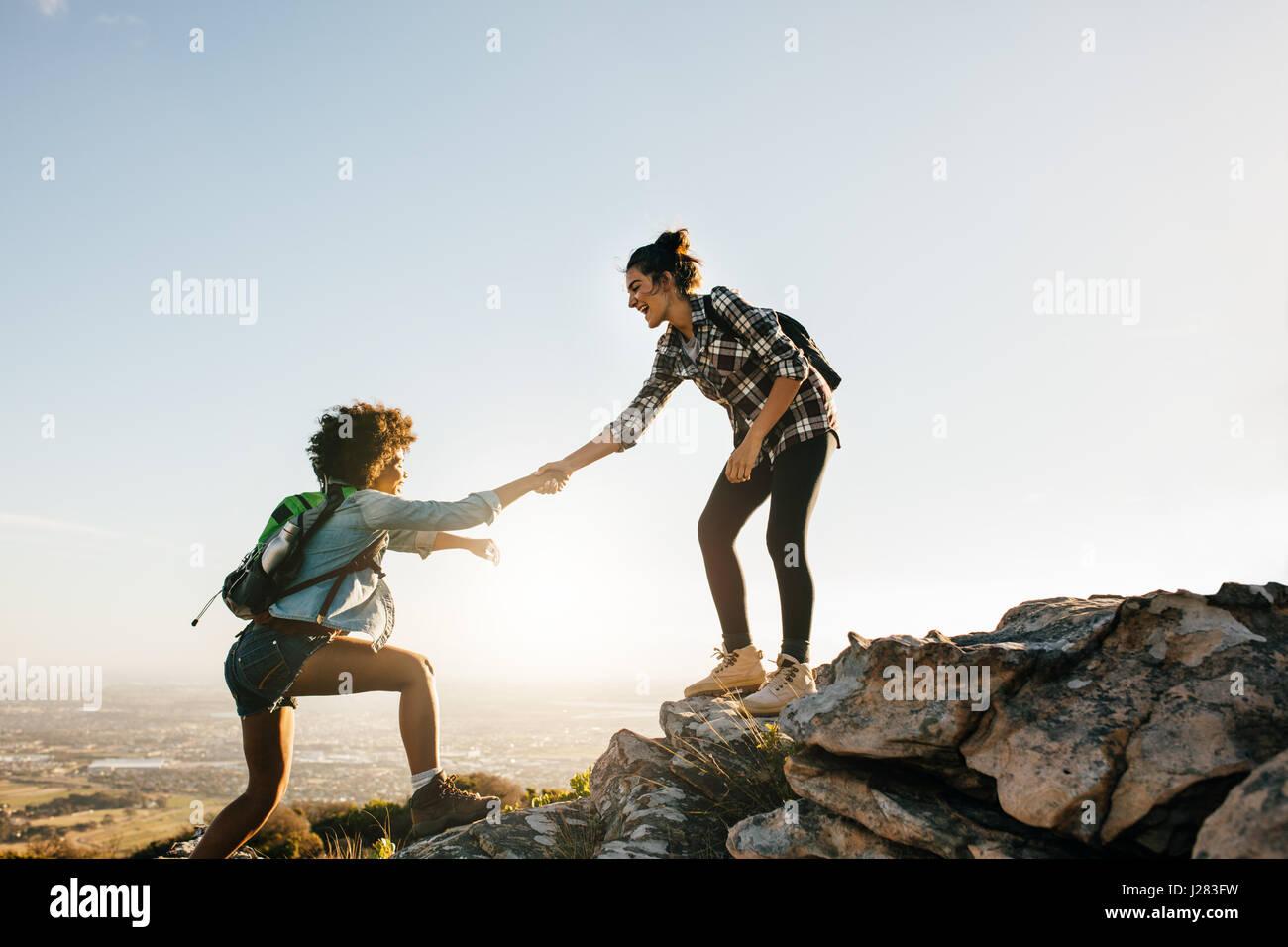 Junge Frau hilft Freund zu dem Felsen erklimmen. Zwei junge Frauen, die in der Natur wandern. Stockbild