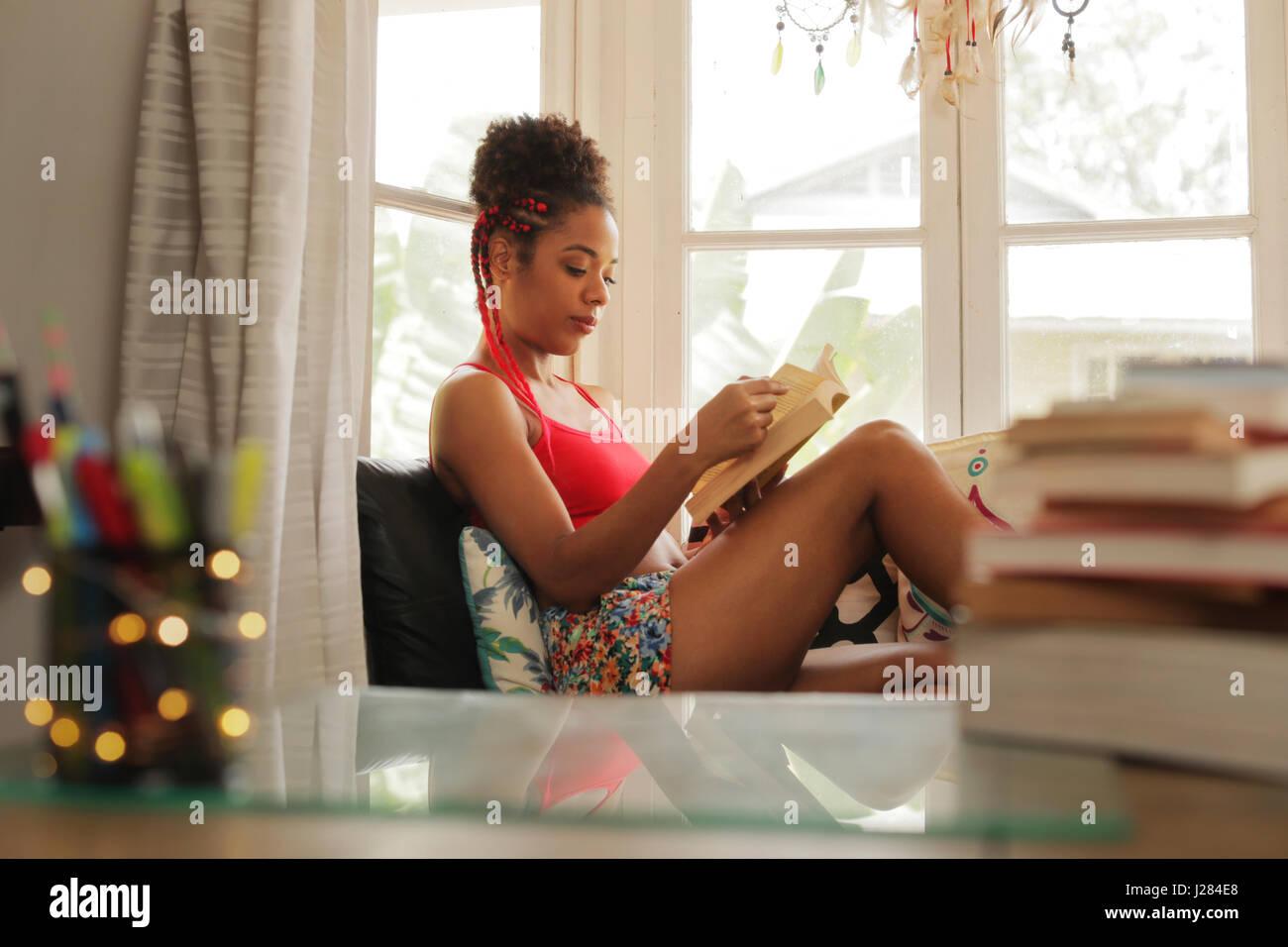 Glückliche Studentin Buch zu lesen und auf Sofa sitzen. Junge afrikanische amerikanische Frau, entspannend, Stockbild