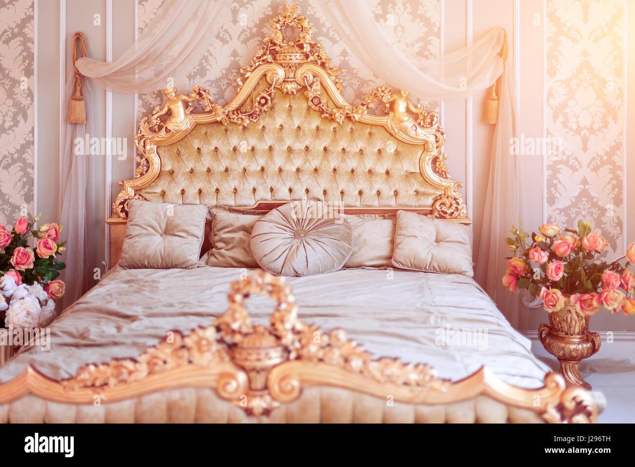 Luxus Schlafzimmer In Hellen Farben Mit Goldenen Möbel Details. Große  Komfortable Doppelzimmer Königsbett In Eleganten Klassischen Interieur.  Getönten Bild