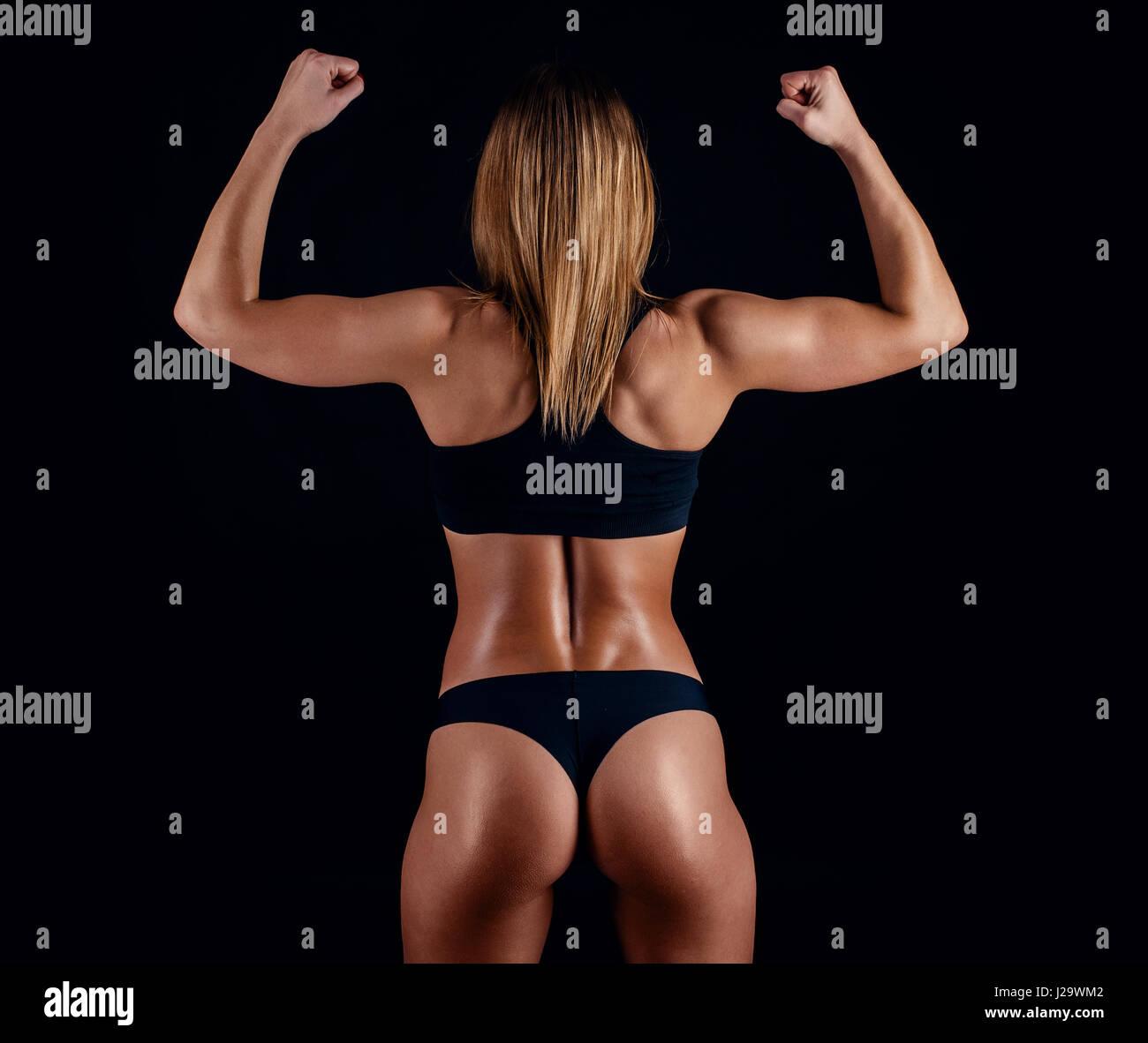 Sportliches Girl mit großen Muskeln im schwarzen Sportbekleidung ...