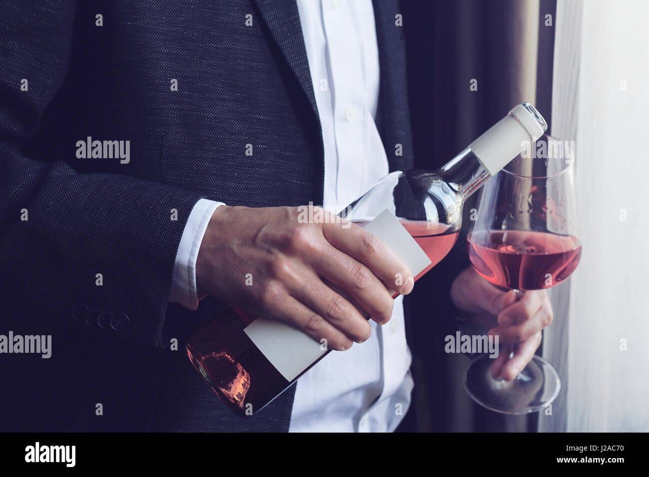 Horizontale Nahaufnahme von kaukasischen Mann im schwarzen Anzug und weißes Hemd strömenden Roséwein Stockbild