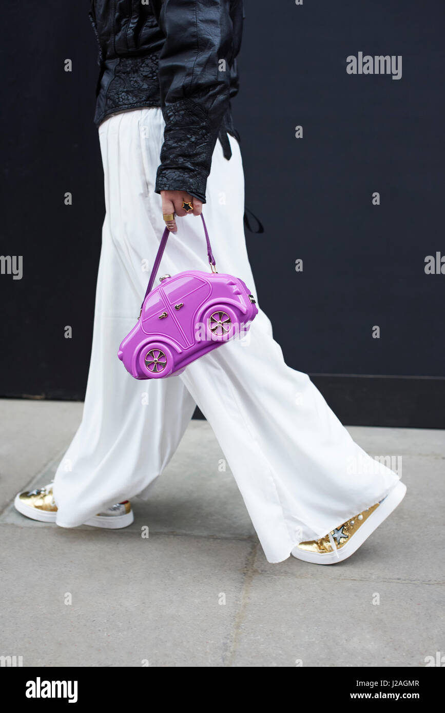 LONDON - Februar 2017: Mittelteil Frau mit blauen Haaren trägt Lederjacke und weißen Hosen halten lila Car-förmige Stockfoto