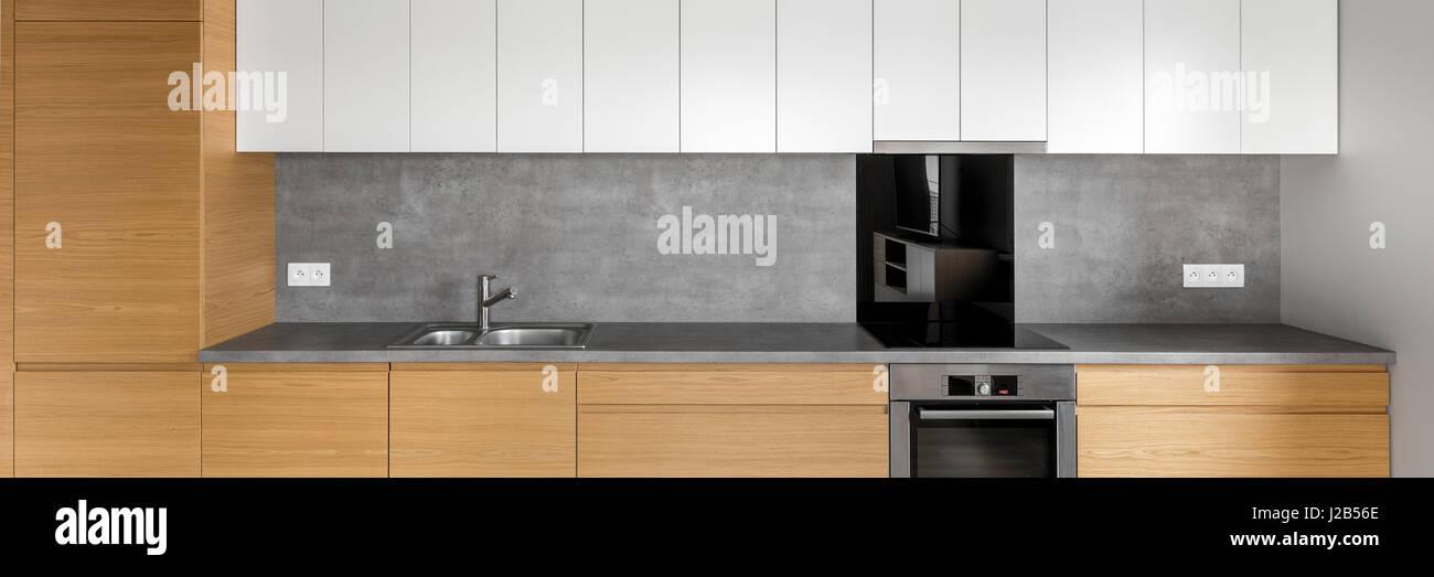 Moderne Küche mit Granit-Arbeitsplatte, weiße Schränke und Betonwand ...