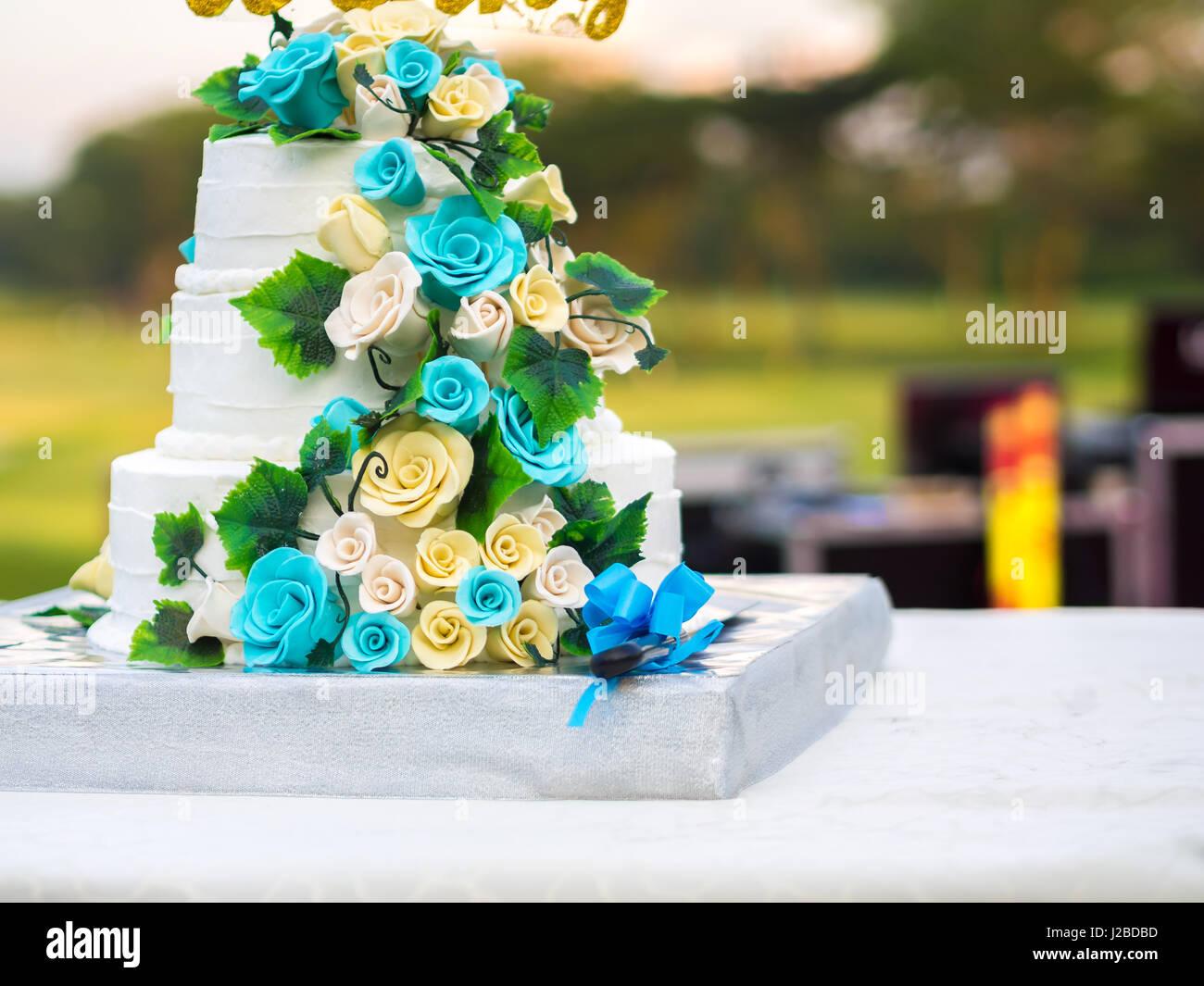 Wunderschöne Hochzeitstorte mit blauen und gelben Rosen Stockbild