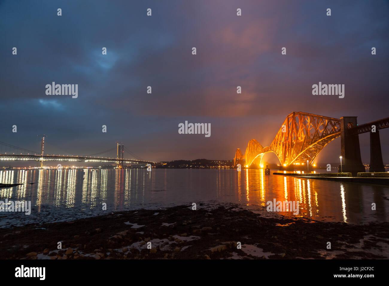 Die Forth Rail Bridge beleuchtet in der Abenddämmerung. South Queensferry, Edinburgh, Schottland Stockbild